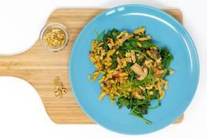 Grünkohl Spätzle mit Pilzen in cremiger Soße auf einem blauen Teller auf einem Holbrettchen mit Walnüssen in der Aufsicht