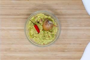 Guacamole Brotaufstrich in Glasschale auf Holztisch von oben fotografiert