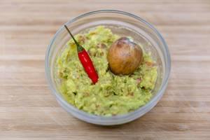 Guacamole in Glasschälchen mit Chilischote und Avocadokern