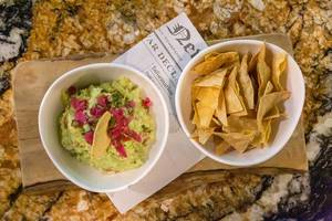 Guacamole made of Avocado, Pico de Gallo and oven baked Tortilla Chips, served on a wooden beam with a Spanish newspaper at Fit Kitchen, Barcelona