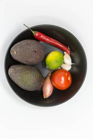 Guacamole Mix Ingredients - Avocados, Tomato, Onion, Garlic, Lime and Chilipepper on balck plate
