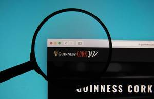 Guinness Jazz Festival logo on a computer screen with a magnifying glass