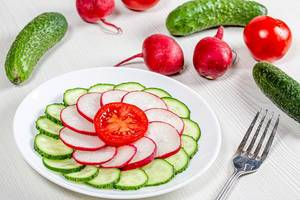 Gurken, Radieschen und Tomaten in Scheiben geschnitten auf einem Teller umgeben von den Zutaten auf einem weißen Tisch