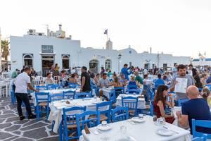 Gut besuchte, typisch griechische Restaurantterrasse in blau-weiß vor traditionellen Gebäuden auf Paros