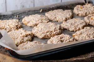Haferflocken Cookie-Dough-Plätzchenteig mit mit Äpfeln und getrockneten Aprikose auf eingefettete Backpapier auf einem Backblech