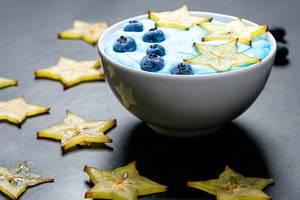 Haferflocken mit gelber Karambole / Sternfrucht und blauen Heidelbeeren in einer Schale auf einem schwarzen Tisch