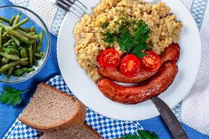 Haferflocken-Porridge mit Bratwürstchen, Tomatenscheiben und rustikalem Brot, auf einem blau-weiß gedeckten Tisch, im Bayrischen Look