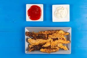 Hähnchen Sticks mit Sesamkruste neben Ketchup und Mayonnaise in Schalen auf einem blauen Tisch aus Holz
