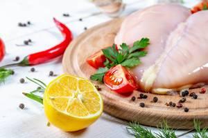 Hähnchenfilet auf Küchenbrett mit Tomaten, Chilis, Pfefferkörnern, Kräutern und halber Zitrone