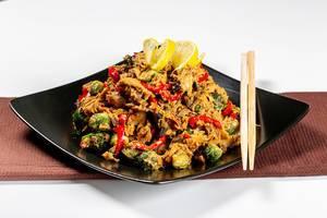 Hähnchenfleisch mit Gemüse, Zitronen und scharfer Soße, neben Essstäbchen