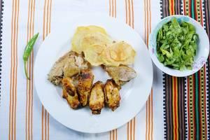 Hähnchenflügel und frittierte Kartoffelscheiben mit grünem Salat auf einer bunten Tischdecke