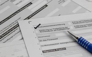 Haken bei Einkommensteuererklärung im Lohnsteuerformular mit losen Antragsblättern und noch auszufüllenden Unterlagen - Nahansicht