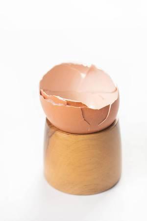 Halbe Eierschalen ohne Ei in Eierhalter aus Holz isoliert vor weißem Hintergrund