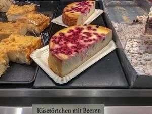 Halbe Käsetörtchen mit Beeren in einer Bäckerei-Auslage