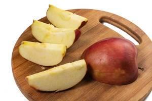 Halber roter Apfel neben vier Apfelschnitzen auf rundem Holzbrett vor weißem Hintergrund