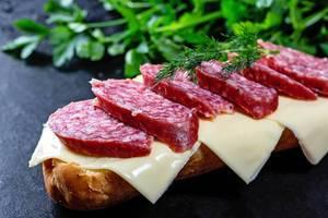 Halbes Sandwich mit Salami, Käse und frischen Kräutern auf schwarzem Untergrund