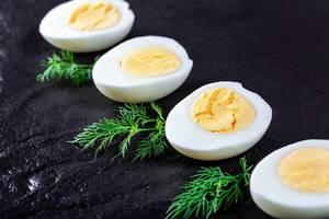 Halbierte, gekochte Eier, auf schwarzem Untergrund, mit grünen Kräutern