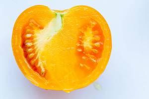 Halbierte, gelbe Tomate auf weißer Oberfläche