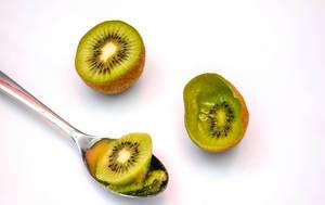 Halbierte Kiwi mit Fruchtfleisch im Löffel