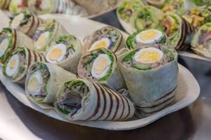 Halbierte Wraps gefüllt mit Thunfisch, hartgekochtem Ei, Oliven und Salat auf Platte