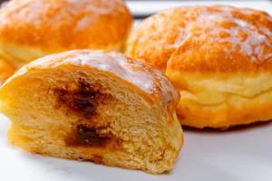 Halbierter Pfannkuchen mit süßer Kondensmilch gefüllt, im Hintergrund weitere Donuts