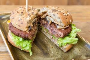 """Halbierter Vitamin B12 - Burger """"Naturbursche"""" von Moving Mountains bei """"Hans im Glück"""", mit Pilzen, Pflanzenbratling und karamellisierten Zwiebelringen"""