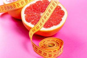 Half of a ripe grapefruit wrapped with measuring tape close-up. Weight loss concept