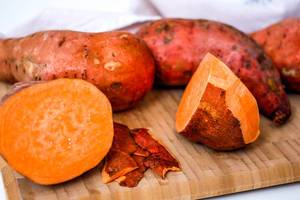 Half peeled and cut sweet potatoes on a  kitchen table