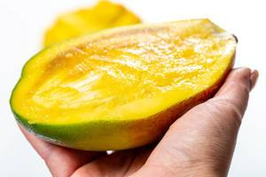 Half ripe mango in female hand close-up (Flip 2019)