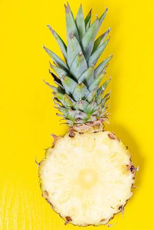 Half ripe pineapple with green leaves on a yellow background (Flip 2019)