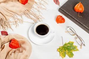 Hallo Herbst: Flatlay von einer Tasse heißen Kaffee mit Brillen, einem geschlossenen Buch und bunten Blättern auf einem Holztisch