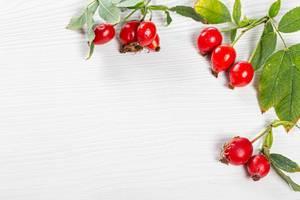 Hallo Herbst: Obene Aufnahme von Hagebutten auf einem Holztisch