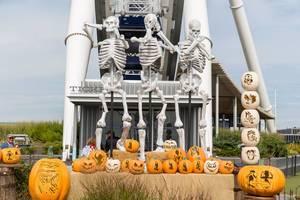 Halloween-Dekoration mit geschnitzten Kürbissen und Skelette im Affen-Emoji Style