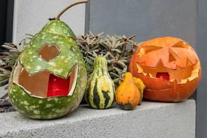 Halloween Kürbisse mit Grimassen vor einem Haus