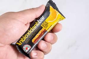 Halt hält einen Antioxidations-Müsliriegel mit Orange und ACE Vitaminen, vor weißem Hintergrund