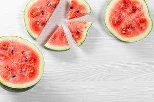Halves and pieces of watermelon on white wooden background. Top view