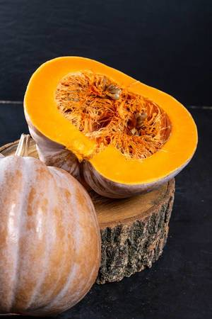 Halves fresh orange pumpkin on stump