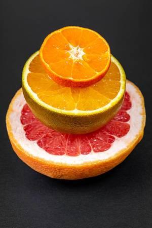 Halves of grapefruit, chocolate orange and mandarin on a black background (Flip 2020)