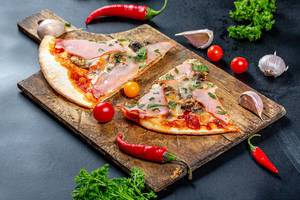 Ham pizza slices on an old wooden kitchen Board with tomatoes, chili and parsley