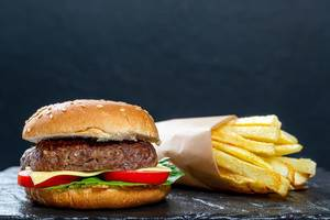 Hamburger and fries on black background