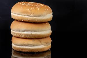 Hamburger Buns above black reflective background with copy space (Flip 2019)