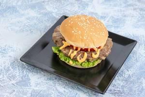 Hamburger mit großem Patty, Burgersauce Tomate und grünem Salat, auf einem schwarzen, quadratischen Teller