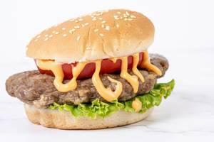 Hamburger with Tomato Lettuce and Sauce above white background (Flip 2019) (Flip 2019)