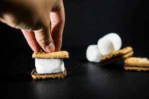 Hand bereitet Smore aus weißem Marshmallow zwischen Keks vor auf schwarzem Hintergrund