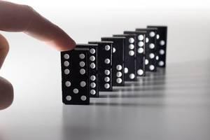 Hand bringt Dominosteine zum Sturz