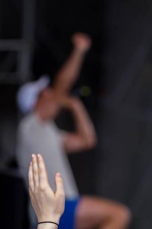 Hand eines Konzertbesuchers und Marteria im verschwommenen Hintergrund