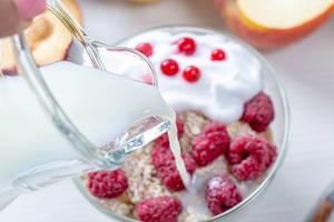 Hand gießt Milch in eine Glasschüssel voll von Haferflocken und Beeren