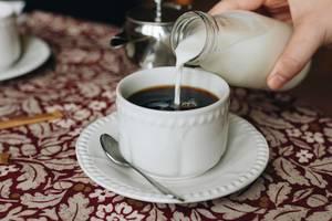 Hand gießt Milch in Kaffee in einem Café
