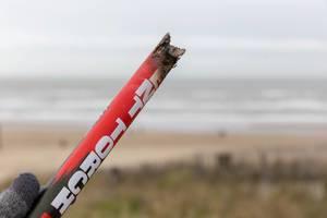 Hand hält abgebrannte Überreste von Silvester-Feuerwerk vor Strand