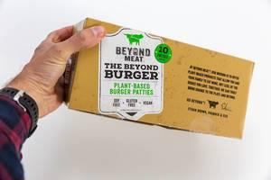 Hand hält Beyond Meat veganische, pflanzliche glutenfreie Burger-Pastetchen in Packung